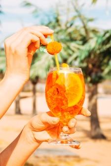 Verre de boisson orange savoureuse juteuse dans les mains