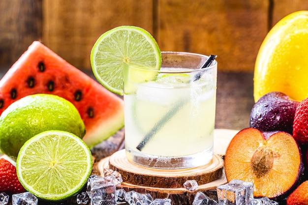 Verre de boisson typiquement brésilienne appelée caipirinha, citron, alcool distillé, cachaça et sucre. divers fruits autour