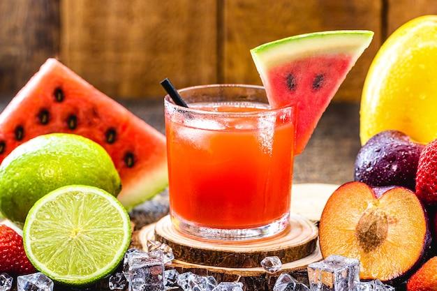 Verre de boisson typiquement brésilienne appelée caipirinha, pastèque, alcool distillé, cachaça et sucre. divers fruits autour