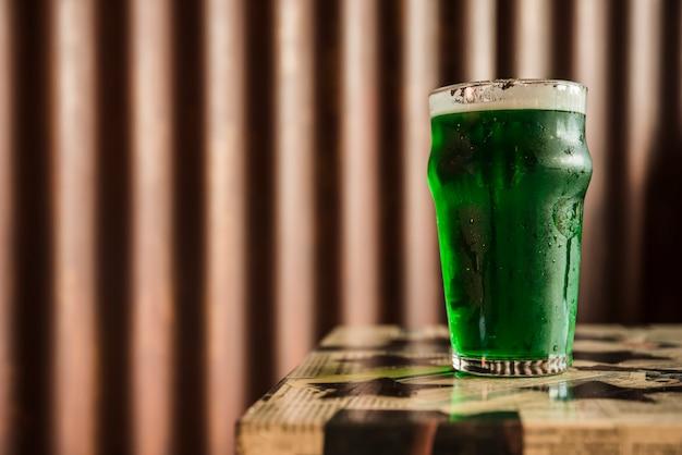 Verre de boisson verte sur la table près d'un mur en bois