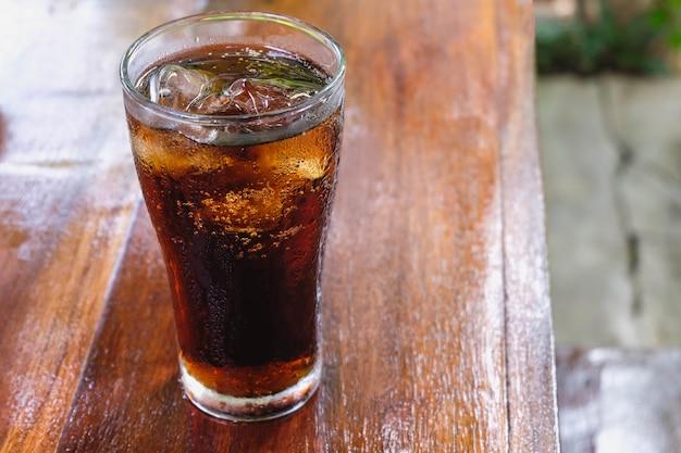 Verre de boissons non alcoolisées et boissons non alcoolisées noires sur la table