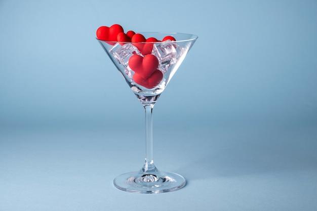 Verre avec des bonbons de sucre en forme de coeur rouge et de la glace. sur fond bleu. concept de saint valentin, anniversaire ou célébration de mariage. copiez l'espace.