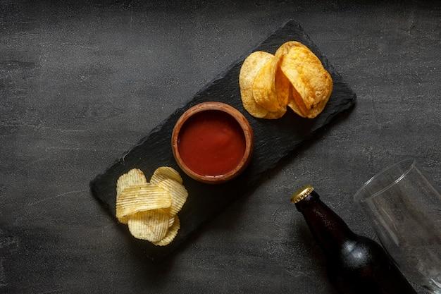 Verre et bouteille de bière avec chips et ketchup aux tomates