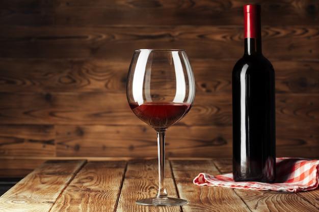 Verre et bouteille avec un délicieux vin rouge sur la table