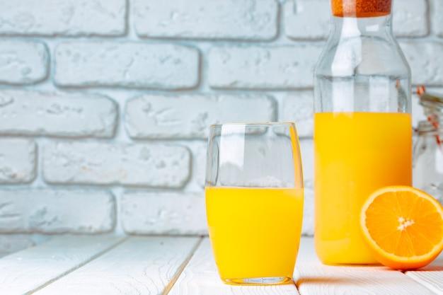 Verre et bouteille de jus d'orange sur fond de brique blanche