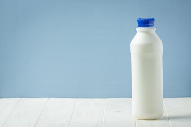 Verre et bouteille de lait sur une surface en bois blanche