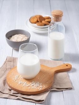 Un verre et une bouteille de lait végétalien frais avec des biscuits à l'avoine sur un fond en bois blanc