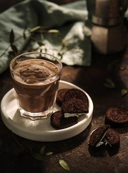 Verre de cacao avec glace au chocolat et biscuits aux pépites de chocolat à la crème blanche. tôt le matin. petit déjeuner.