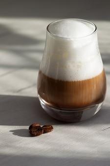 Verre avec café au lait au lait ou cappuccino le matin. lumière du soleil, bonne journée.