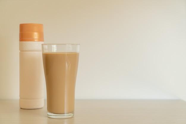Verre à café au lait avec des bouteilles de café prêtes à boire sur la table