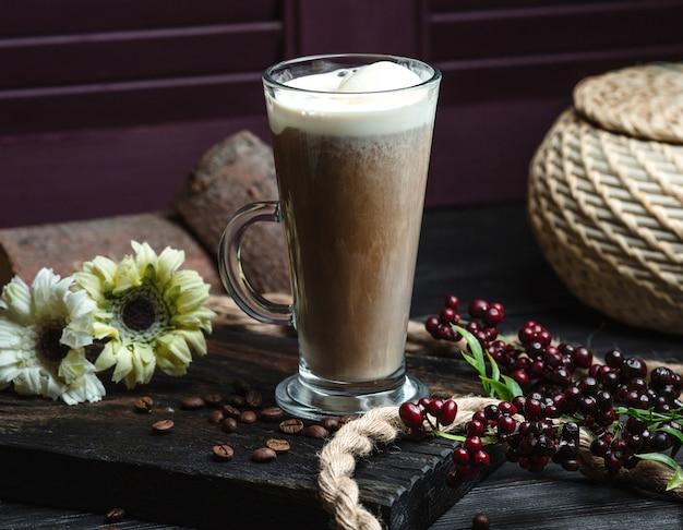 Verre de café au lait avec mousse décoré avec des grains de café et des fleurs