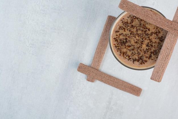 Verre de café avec des biscuits bâton sur fond gris. photo de haute qualité