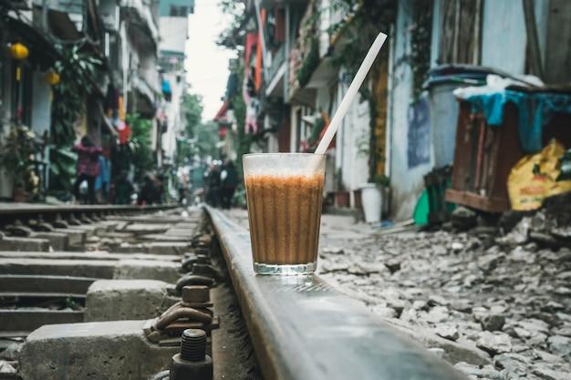 Un verre de café brun froid est sur le chemin de fer à hanoi. viêt nam. l'une des attractions de hanoi - un train passant entre les vieilles maisons dans une rue étroite de la ville.