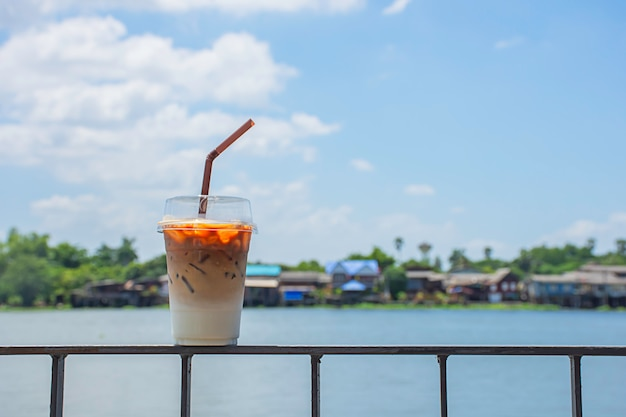Verre de café froid sur le balcon en fer avec vue sur la rivière et la maison.