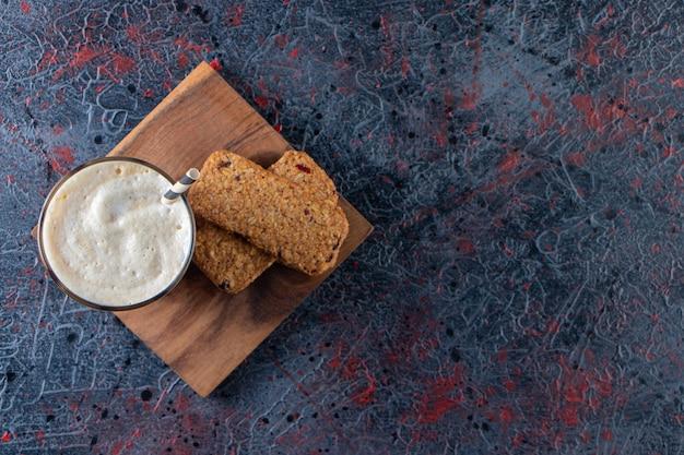 Verre de café froid mousseux avec biscuits sur plaque de bois.