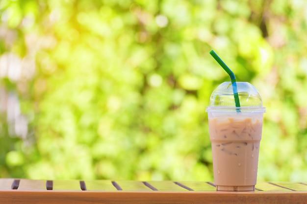 Verre de café glacé sur beau fond naturel vert.