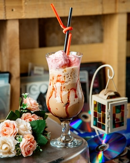 Un verre de café glacé garni de coton doux en rose