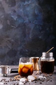 Verre de café glacé avec des glaçons servis avec de la crème, du cezve de cuivre et des grains de café sur un mur sombre