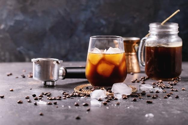 Verre de café glacé avec des glaçons servis avec de la crème, du cezve de cuivre et des grains de café sur une surface sombre