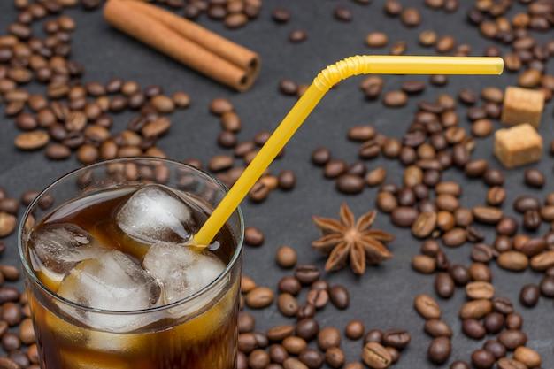 Verre de café glacé, paille jaune. sur fond noir, grains de café, bâton de cannelle, anis étoilé.