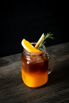 Un verre de café noir américain glacé et une couche de jus d'orange et de citron décoré de romarin et de cannelle