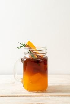 Un verre de café noir americano glacé et couche de jus d'orange et de citron décoré de romarin et de cannelle sur table en bois
