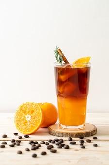 Un verre de café noir americano glacé et une couche de jus d'orange et de citron décorés de romarin et de cannelle sur une table en bois
