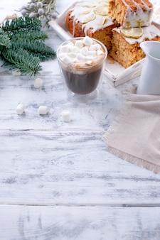 Verre à café et petites guimauves, gâteau au citron et branche d'arbre de noël
