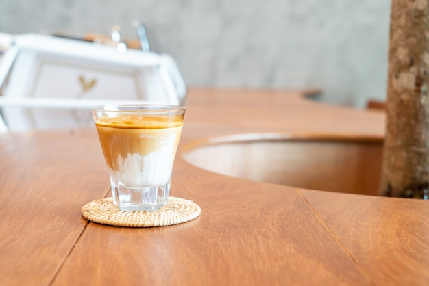 Verre à café sale (lait froid garni de café expresso chaud) dans un café