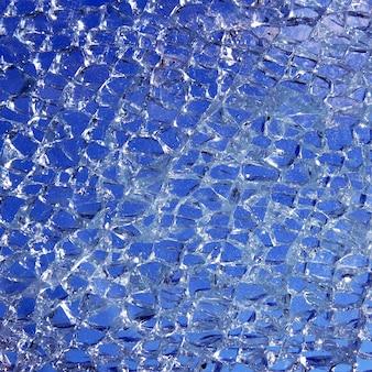 Verre cassé fissuré sur fond bleu