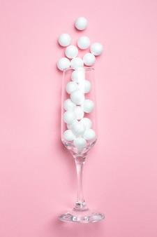 Verre de champagne avec des boules blanches sur le style minimal rose.
