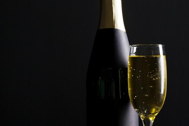 Verre à champagne et bouteille sur fond noir