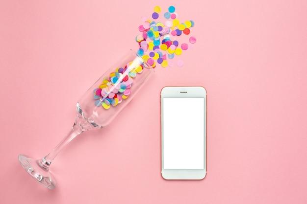 Verre de champagne avec des confettis multicolores et un téléphone portable et sur une table pastel rose