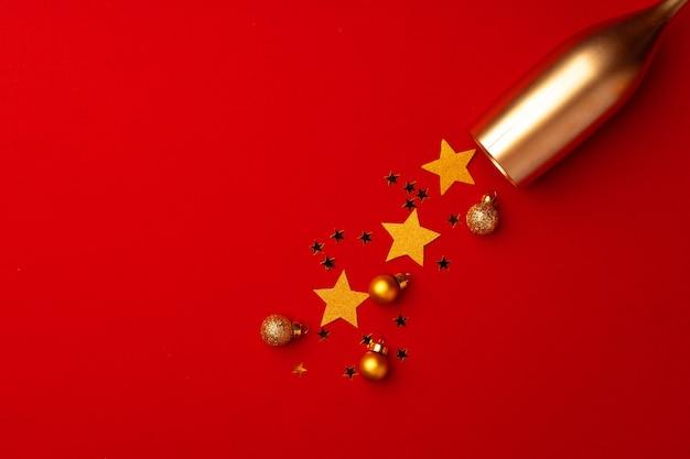 Verre à champagne avec des confettis de paillettes sur fond rouge vue de dessus plat