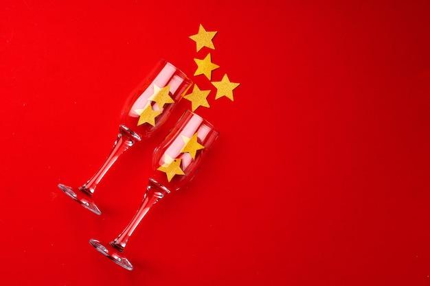 Verre à champagne avec des confettis de paillettes sur la vue de dessus plat rouge