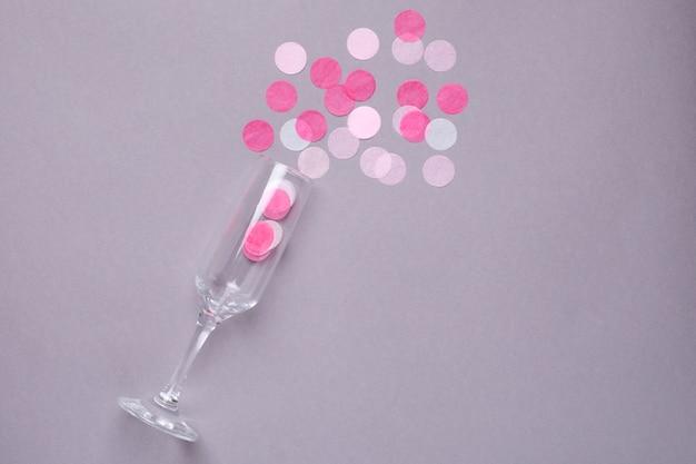 Verre de champagne avec des confettis roses sur un gris