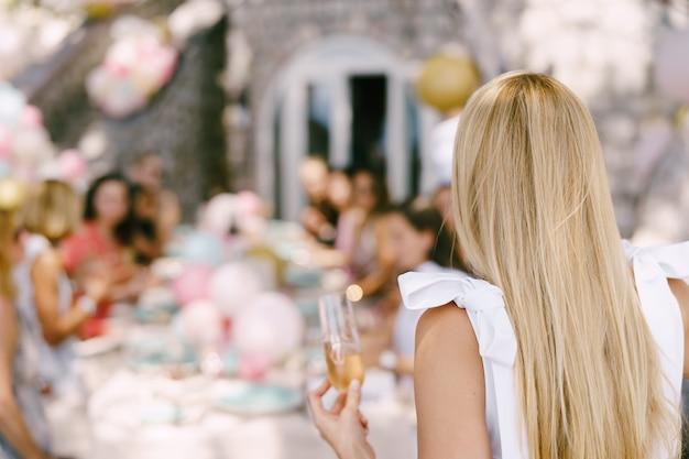 Verre de champagne dans la main d'une fille dans le contexte d'une table servie avec des invités