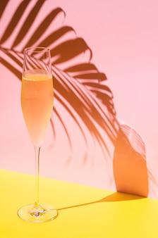 Un verre de champagne froid avec de la vapeur qui a une ombre de feuille de noix de coco du concept d'été à la lumière du soleil
