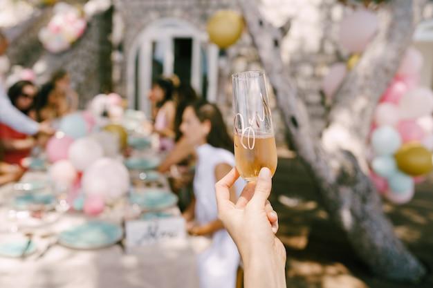 Verre de champagne à la main dans le contexte d'une table servie avec des invités