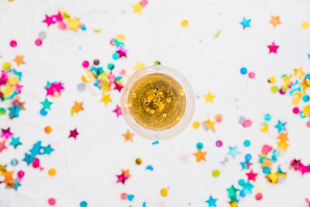 Verre de champagne avec des paillettes sur la table