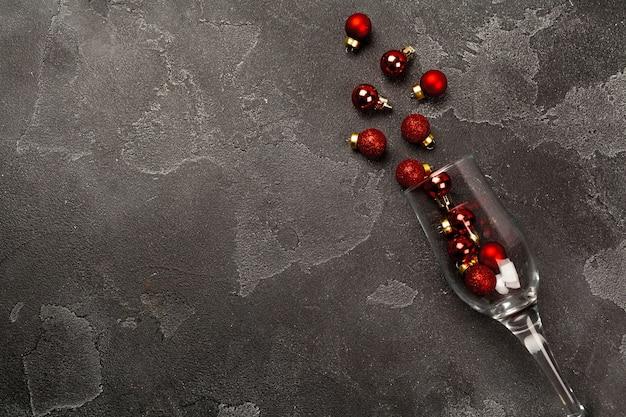 Verre à champagne avec de petites boules de noël dispersées vue de dessus