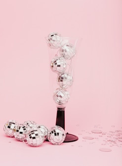 Verre à champagne rempli de boules de noël en argent