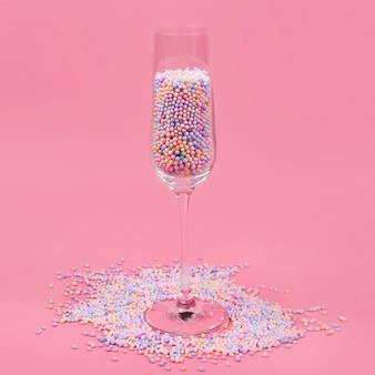 Verre à champagne rempli de boules de sucre colorées sur rose