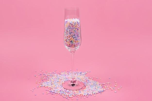 Verre à champagne rempli de boules de sucre colorées