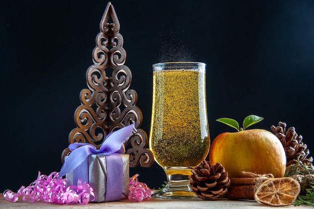 Verre de champagne vue de face avec pomme de cônes et cadeaux lors d'une soirée de boisson de couleur sombre