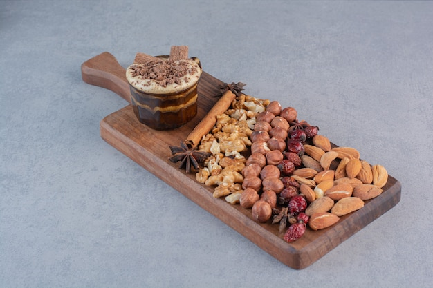 Un verre de chocolat chaud avec tas de noix diverses sur planche de bois.