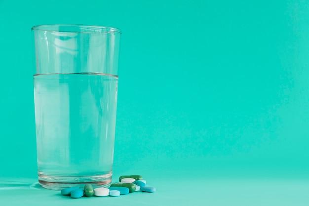 Verre clair d'eau avec des pilules sur fond turquoise