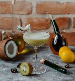 Un verre de cocktail alcool au lait de coco avec un arôme de kiwi.