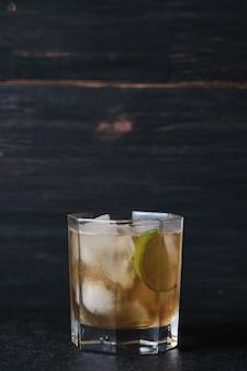 Verre avec un cocktail alcoolisé sur une table dans un bar. whisky avec glace garni de citron vert.