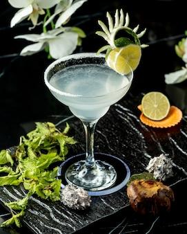 Verre de cocktail au citron vert garni d'une tranche de citron vert et d'un zeste